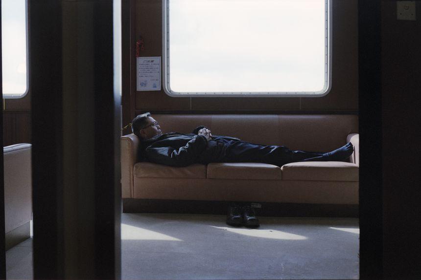 A man who looks a little like Kenzaburo sleeps, passenger ship to Hiroshima