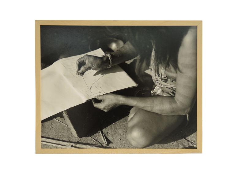 Sans titre [Femme reproduisant des peintures corporelles sur une feuille de papier]
