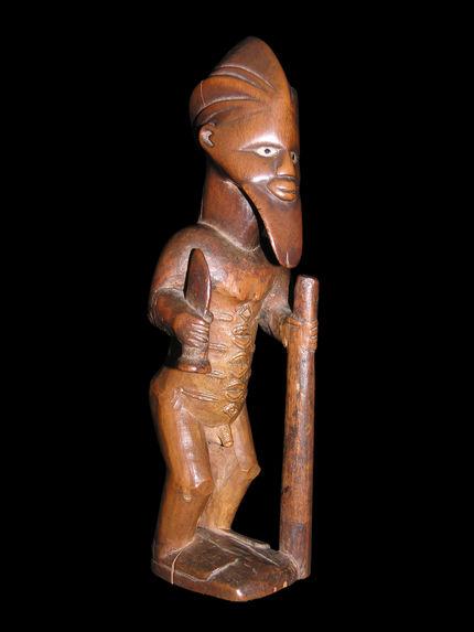 Statuette masculine debout tenant un bâton et un coutelas