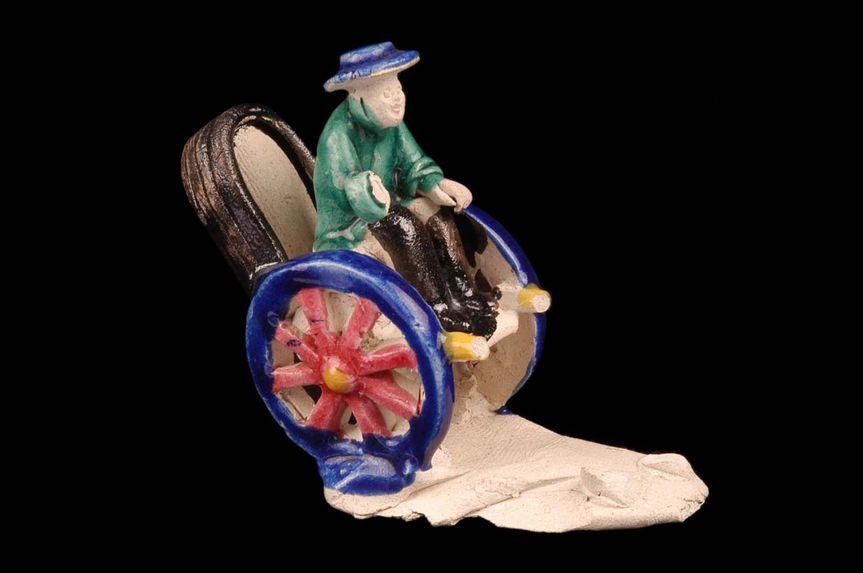 Figurine représentant un personnage assis dans un pousse-pousse