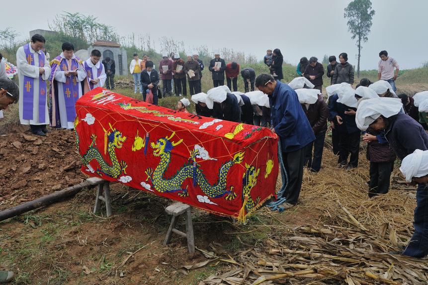 Une linceul [sic] rouge avec une paire de dragons brodés recouvre un cercueil