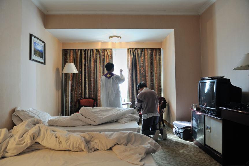Chaque matin, le père célèbre la messe avec un coreligionnaire dans la chambre de l'hôtel de voyage