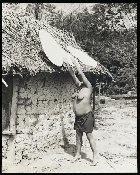 Sans titre [femme installant des galettes de casabe sur le toit d'une maison afin de les faire sécher]